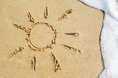 Sun-Zeichnung gezeichnet auf einen Strand auf dem goldenen Sandhintergrund mit Seewelle und Schaum auf Sommerferien am Erholungso lizenzfreie stockfotografie