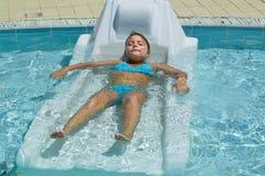 采取sunbath和放松在室外温泉游泳池床上的好的特写镜头观点的一个相当迷人的小女孩 免版税库存照片