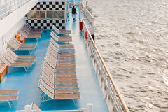 Sunbath chairs on side of cruise liner at morning Stock Image