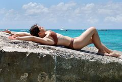 The Sunbath On A Concrete. The girl is having a sunbath on a concrete mall on Grand Turk island, Turks & Caicos stock image