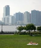 Sunbath girls. In a quiet New Park park opposite of buildings separated by the see Royalty Free Stock Photo