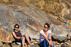 Sunbath on the rocks. Two young women lying on the rocks in a sunny day Royalty Free Stock Photo
