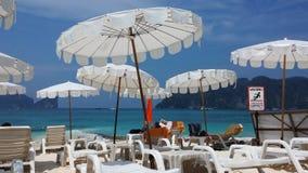 Sunbath-Stühle und tiefes blaues Meer stockbild