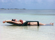 Sunbath In A Water. The girl in sunglasses is having a sunbath laying on a chair in water on Grand Turk island beach, Turks & Caicos royalty free stock photo