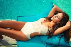 Sunbath. Woman relax by the pool take sunbath sunny summer day stock photo