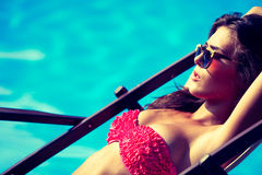 Sunbath. Woman with sunglasses take sunbath by the swimming pool hot summer day Royalty Free Stock Image