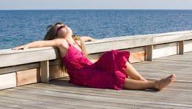 Sunbath on the wooden deck. Girl having sunbath on the wooden deck stock images