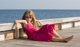 Sunbath on the wooden deck. So seriouse. Girl sitting on the wooden deck very seriouse Stock Photos