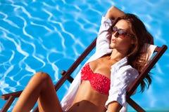 Sunbath. Young beautiful woman in bikini and sunglasses by the pool take sunbath royalty free stock photo