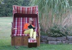 Sunbathe w zadaszającym łozinowym plażowym krześle i czyta podniecającą książkę, więc ty możesz wydawać wakacje zdjęcia royalty free