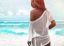 Sunbathed kobieta model w przejrzystym białym bluzki obsiadaniu na lata plażowym i błękitnym oceanu tle zdjęcia royalty free