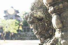 Sunbathened облицовывает статую духа на виске Pura Samuan Tiga, Ubud, Бали, Индонезии Стоковое Изображение