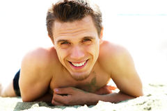 Sunbather. Photo of smiling guy lying on beach and looking at camera while sunbathing Stock Photography