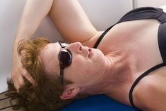 Sunbather. Woman in the sun on a sailboat stock image