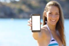 Sunbather montrant l'écran vide de téléphone sur la plage Photographie stock libre de droits
