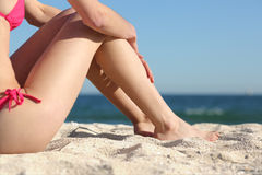 Sunbatherkvinnan lägger benen på ryggen sammanträde på sanden av stranden Royaltyfri Fotografi