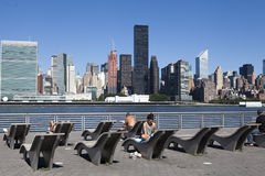 Sunbathers enjoying the New York skyline. This is a picture of sun sunbathers enjoying the sun and the New York skyline. It was taken in Gantry Park in Queens Stock Images