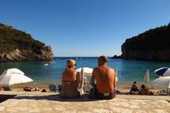 Sunbathers beside Mediterranean Sea sheltered cove. Corfu, Greece - September 3, 2014: A man and woman chat beside the beach at Paleokastritsa on Corfu, Greece Royalty Free Stock Image