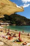 Sunbathers on sandy Mediterranean beach Greek island of Corfu. Corfu, Greece - September 3, 2014: Sunbathers relax on a sandy beach on the Greek island of Corfu Stock Photo