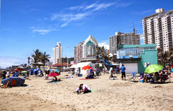 Sunbathers Soaking up Sun on Durban Beach, South Africa Stock Image