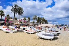 Sunbathers w Platja melinie Bossa wyrzucać na brzeg w Ibiza miasteczku, Hiszpania Zdjęcie Stock