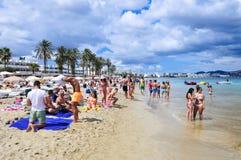 Sunbathers w Platja melinie Bossa wyrzucać na brzeg w Ibiza miasteczku, Hiszpania Obrazy Stock