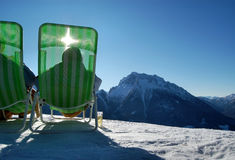 Sunbathers on wintry mountain. Rear view of two sunbathers sat in colorful deckchairs on wintry mountain, Bavarian Alps, Germany Royalty Free Stock Photos