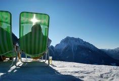 Sunbathers on wintry mountain Royalty Free Stock Photos