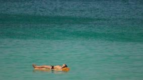 Sunbathes in ocean stock footage