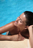 Sunbathing. Woman at the pool royalty free stock image