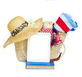 Sunbathing accessories in basket with tablet Royalty Free Stock Image