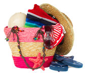 Sunbathing accessories in pink straw bag Royalty Free Stock Photo