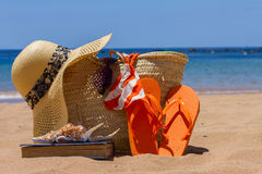 Sunbathing accessories on sandy beach in straw bag Stock Image