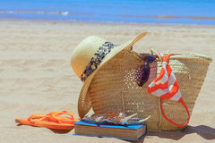 Sunbathing accessories on sandy beach in straw bag Stock Photo