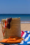 Sunbathing accessories on sandy beach in straw bag Royalty Free Stock Photography