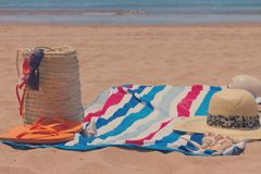 Sunbathing accessories on sandy beach in straw bag Royalty Free Stock Photos