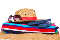Sunbathing accessories and straw hat on sand Royalty Free Stock Photo