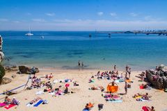 Sunbathing on the beach in Cascais, Portugal. People sunbathing on the beach in Cascais, Portugal royalty free stock image