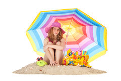 Sunbathing at the beach with colorful parasol. Woman sitting at the beach with pink hat under colorful parasol isolated over white background Royalty Free Stock Image