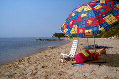 Sunbathing chair and the lost summer. A sunbathing chair, an umbrella and the lost summer royalty free stock images