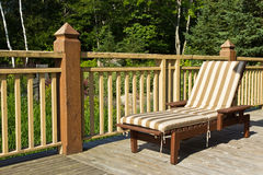 Sunbathing chair on a wooden deck Stock Images