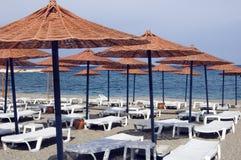 Sunbathing chairs and sun umbrellas Stock Photos