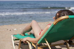 Sunbathing on chaise. Young woman sunbathing on the chair near the ocean stock photos
