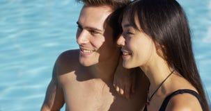 Sunbathing couple sit beside swimming pool Stock Photos