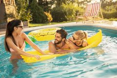 Sunbathing on a floating mattress. Group of friends at a poolside summertime party,  having fun in the swimming pool, sunbathing on a floating mattress stock photos