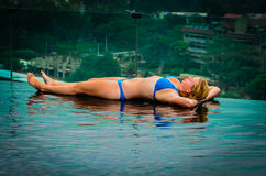 Sunbathing Girl on Edge of Infinity Pool Royalty Free Stock Images