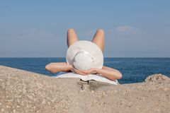 Sunbathing girl. Female person in white hat and white swimwear lying on concrete tetrapod with knees bent and hands behind head royalty free stock photo