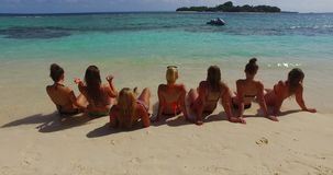 V12719 sunbathing group of young beautiful girls on white sand beach in aqua blue clear sea water and sky stock video