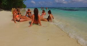 V12707 sunbathing group of young beautiful girls on white sand beach in aqua blue clear sea water and sky Stock Images