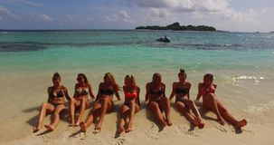 V12721 sunbathing group of young beautiful girls on white sand beach in aqua blue clear sea water and sky Stock Image